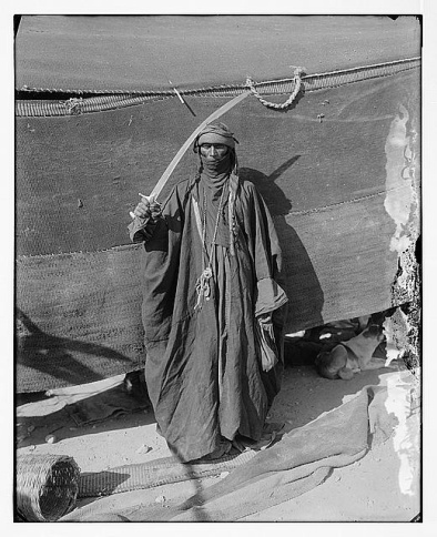 Figure 3B: A Bedouin woman brandishing her sword in preparation for a traditional sword dance. How many women would viciously beat their wives if they saw such a wife at `Eid festivities? Is it any wonder, Salafiyyah banned these ceremonies at `Eid street celebrations.